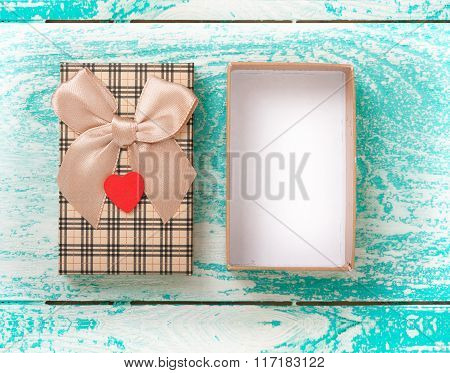Open gift box on blue vintage wooden desk top view.