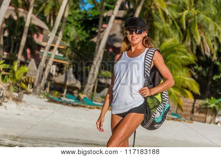 outdoor portrait of strong woman in sportwear ready for workout stretching on tropical beach at sunset. Female sporty muscular body. Dawn bright sunny light.