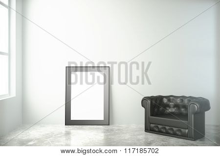 Blank Black Picture Frame On Concrete Floor With Leather Chair In Empty Room, Mock Up