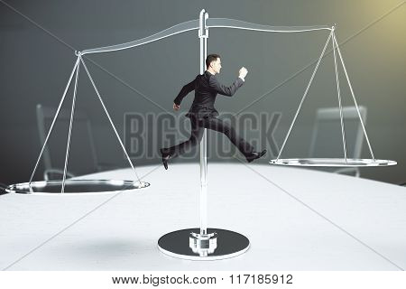 Balance Concept With Businessman Tries To Keep His Balance On The Scales