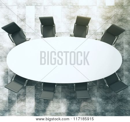 White Oval Conference Table With Black Leather Chairs On Concrete Floor