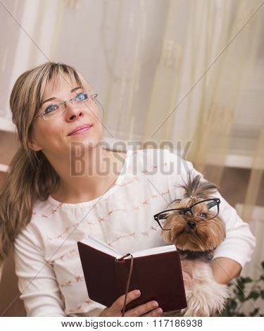 Cheerful Woman Reading With The Yorkshire Terrier