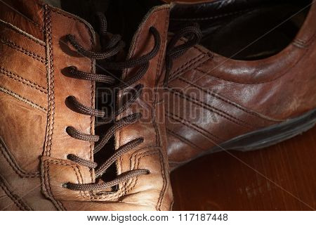 Part Of Old Shoes With Laces On Wooden Floor