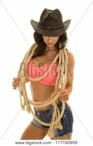 Cowgirl In Denim Shorts And Pink Sports Bra Rope Around Neck Look Down