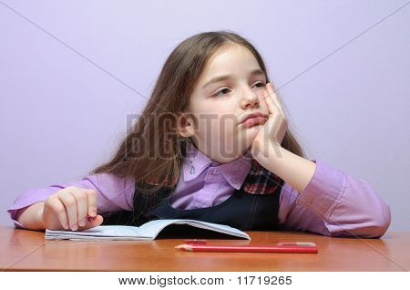 Tired Little School Girl Doing Homeworks At Desk
