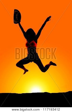 Silhouette Of Cowgirl Jump With Hat Off In Sunset
