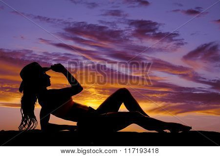 Silhouette Of Cowgirl Lay Back On Elbow Hand On Hat