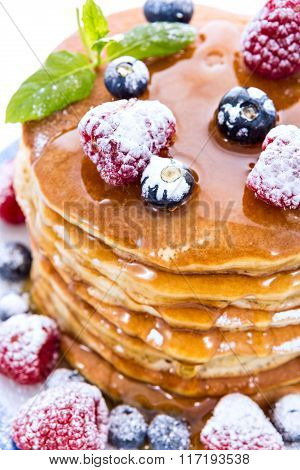 Pile Of Pancakes With Blueberries And Raspberries Sprinkled With Icing Sugar And Poured On With Hone