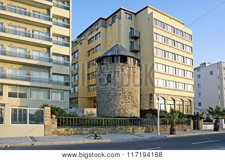 Old Fortress Tower  Among Houses Of Mid-twentieth Century