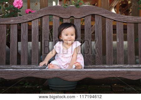 Japanese baby girl sitting on the bench