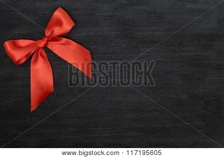 Red Satin Ribbon With Bow Isolated Over Black Background.