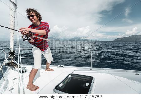 Man fishing in a sea from a sail boat