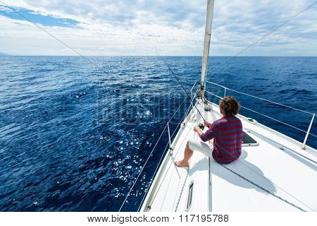 Man fishing in a calm sea from a sail boat