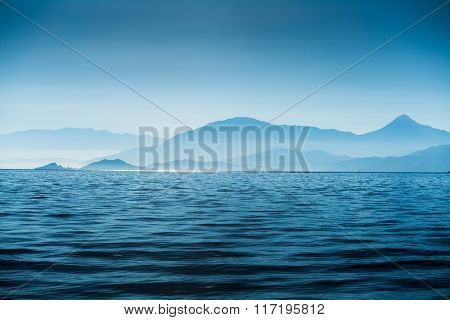 Calm sea with waves and mountains on the horizon. Fethiye town area. Turkey