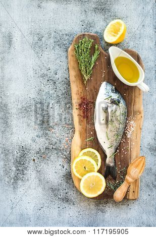 Fresh uncooked dorado or sea bream fish with lemon, herbs, oil and spices on rustic wooden board ove