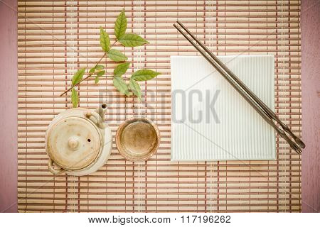Set Chopsticks And Dish With Asian Teapot And Tea Cup On Wooden Background.