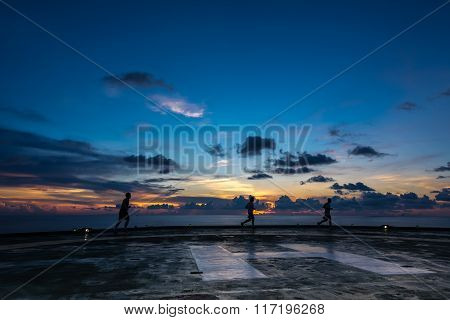 Three men running on oil and gasl rig helipad in Gulf of Thailand in sunset time with helipad light on