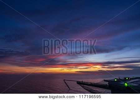 Empty oil and gas rig helipad in sunset time when green edge light on