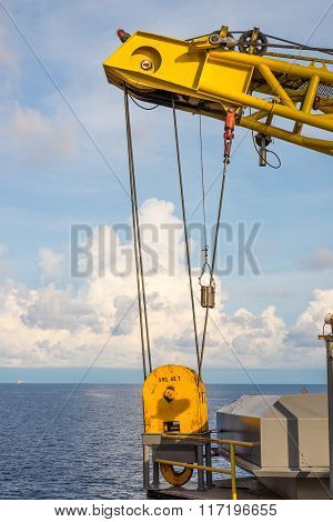 Yellow oil rig crane hoist at storage