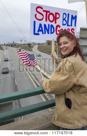 Woman Holds Political Sign On Overpass.