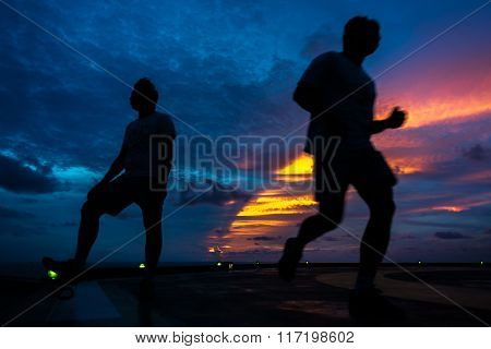 Silhouette of two men on the jack up oil rig helipad with dramatic sun ray in the sky