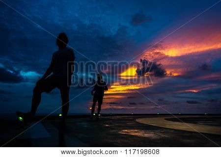 Silhouette of two men on the jack up oil and gas rig helipad when edge light on with dramatic sun ray in the sky