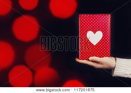 Hand holding red gift isolated on black