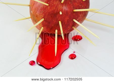 red apple stab by toothpicks and red liquid flow