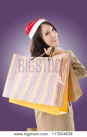 Happy shopping girl holding bags and wearing Christmas hat, half length closeup portrait.