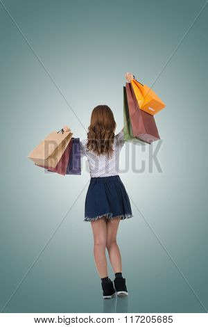 Rear view of Asian shopping woman holding bags, full length portrait isolated.