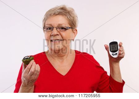 Happy Senior Woman Holding Glucometer And Fresh Cupcake, Measuring And Checking Sugar Level, Concept