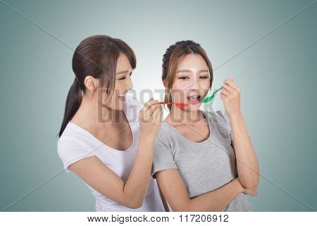 Asian woman with her friend play with spoon.
