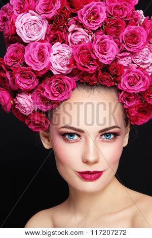 Portrait of young beautiful happy smiling woman with stylish make-up and wig of roses