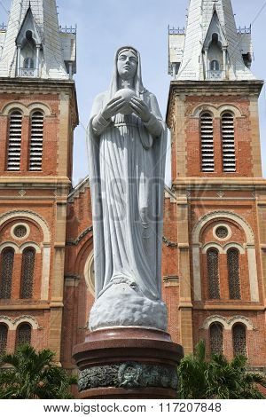 The sculpture of the virgin Mary on the background of the towers of Notre Dame Cathedral