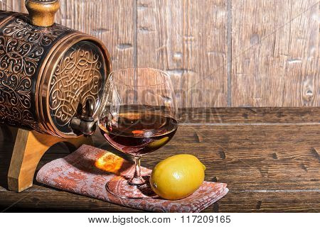 Barrel With Lemon And A Glass Of Cognac On The Old Table