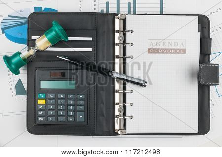 Pen, Calculator On Notebook And Hourglass