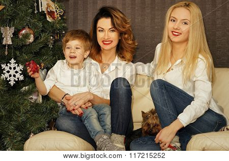 Beautiful Family On The Sofa Near Christmas Tree