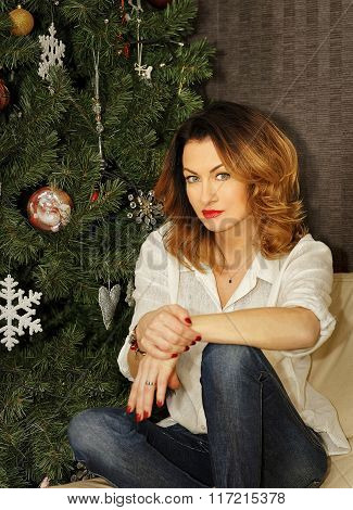 Beautiful Young Woman Sitting On The Sofa Near Christmas Tree