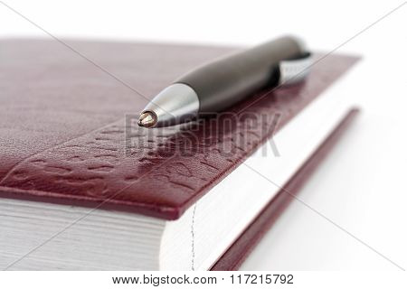 Closeup Black Ballpoint Pen Lying On The Leather Cover