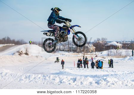 side view of jump and flight of motorcycle racer over snowy track