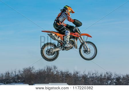 high flying motorcycle racer on blue sky background
