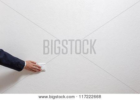 Man's hand turns off the light
