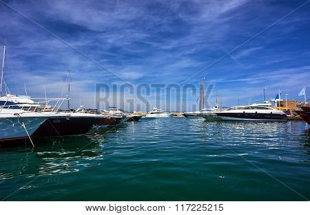 Sailboats and yachts moored to the quay port of Saint-Tropez