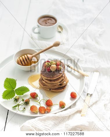 Breakfast set. Buckwheat pancakes with fresh garden strawberries, honey and cup of coffee over white
