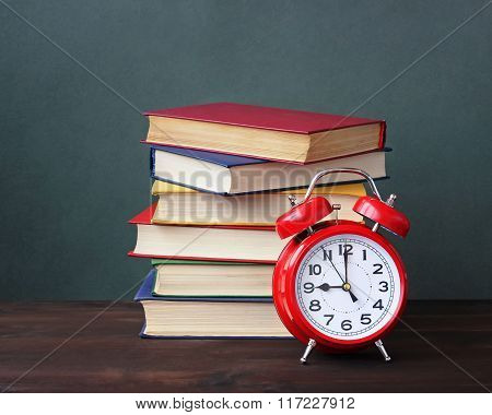 Pile Of Books And Red Alarm Clock.
