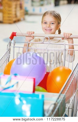 Little smiling girl with trolley at the shop.