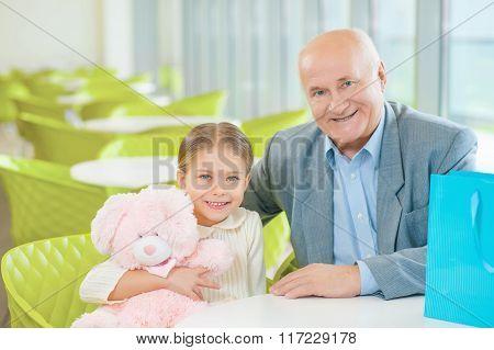 Little cute granddaughter got a present from grandfather.