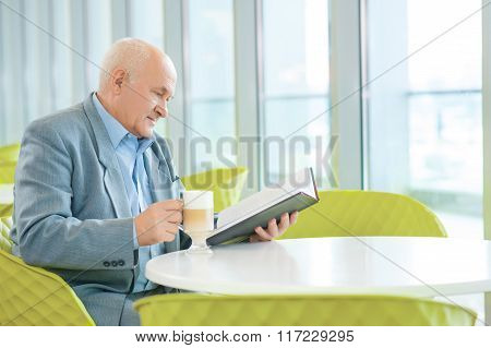 Mature wise man reading a book.