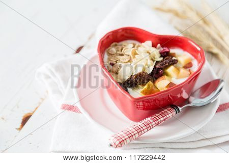 Musli in heart shaped bowl, white wood background