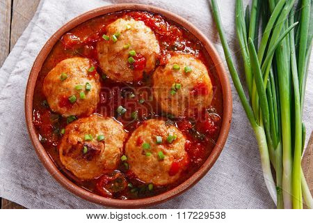 Chicken meatballs with tomato sauce in a clay bowl